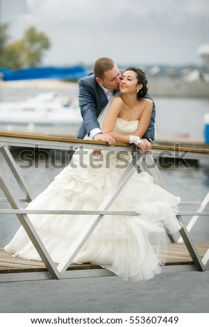 Young couple in love the bride and groom with a bouquet posing on a background pier with yachts, wedding day in the summer. Enjoying a moment of happiness and love