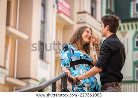 Young couple in love traveling around the beautiful city. Young people hugging and kissing on the streets.Young couple in love, hugging on the street.Happy young couple kissing on the city street. - stock photo