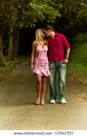 young couple in love walking and kissing - stock photo