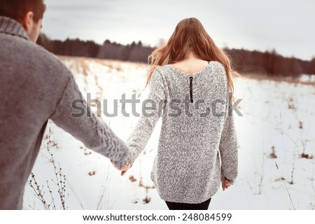 Young couple in love walking in cold winter field holding hands of each other Man fallowing girl