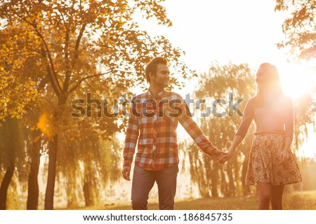 Young couple in love walking in the autumn park holding hands - stock photo