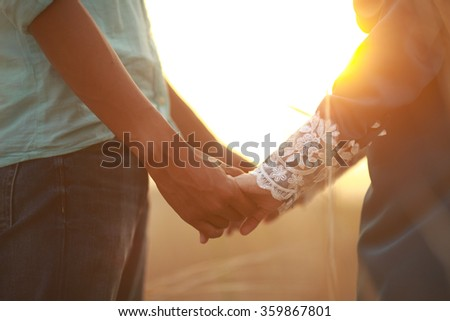 Young couple in love walking in the autumn park holding hands looking in the sunset. selective focus. shallow dof. - stock photo