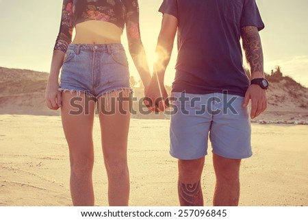Young couple in love walking in the park holding hands looking in the sunset  - stock photo