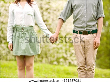 Young couple in love walking in the spring park holding hands looking in the sunset - stock photo