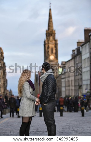 Young couple in love walking on the Royal Mile in Edinburgh - stock photo