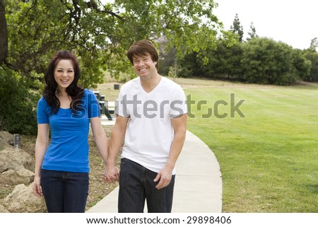 Young couple in love walking through a park