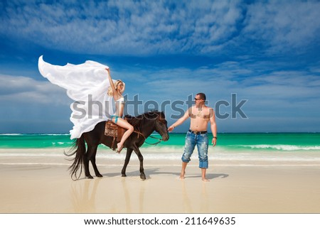 Young couple in love walking with the horse on a tropical beach. Tropical sea in the background. Summer vacation. - stock photo
