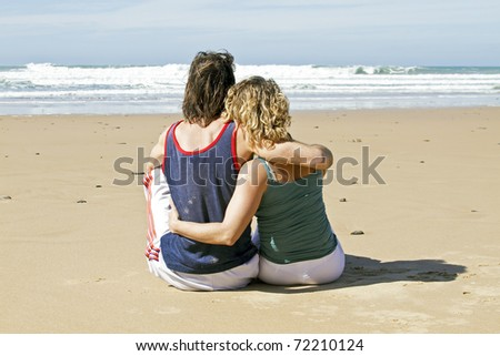 Young couple in love watching the ocean - stock photo