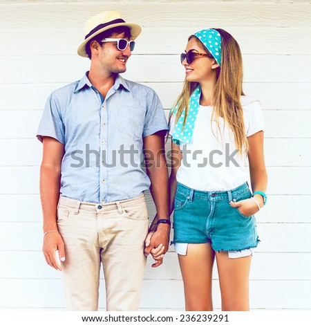 Young couple in love wearing vintage clothing hat and sunglasses, holding hands and posing at white wooden background. Vintage instagram coors. - stock photo