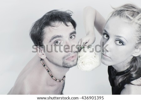 Young couple in love with a white rose and silver make-up closeup