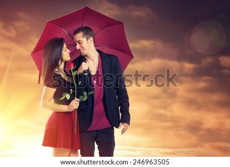 Young couple in love with red umbrella and flower over sunset sky - stock photo