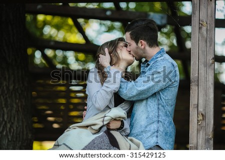 Young couple in love wrapped in plaid standing and kissing