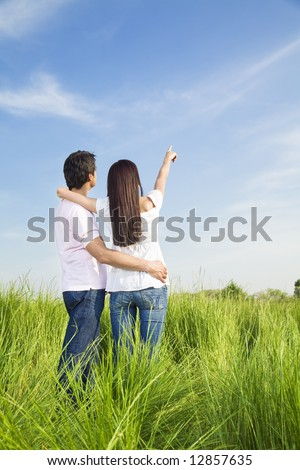 young couple in meadow with hand in air, hugging and smiling. Copy space - stock photo