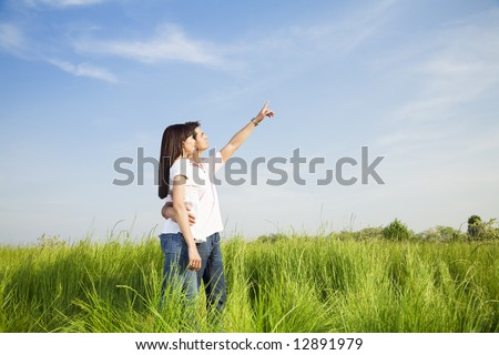 young couple in meadow with hand in air, hugging. Copy space - stock photo