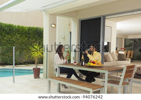 Young couple in modern backyard enjoying champagne and strawberries - stock photo