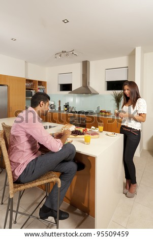 Young couple in modern kitchen with food platter