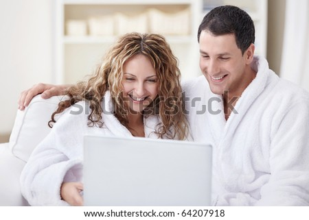 Young couple in overalls looking at laptop - stock photo
