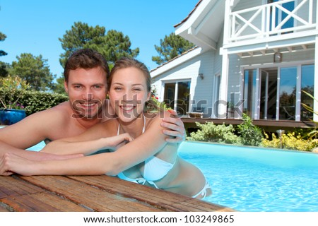 Young couple in private swimming pool - stock photo