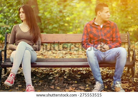Young couple in quarrel sitting on bench in park - stock photo