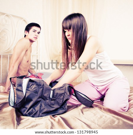 Young couple in quarrel. The girl collects things - stock photo