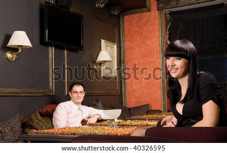 Young couple in restaurant. She is smiling and seducing him - stock photo