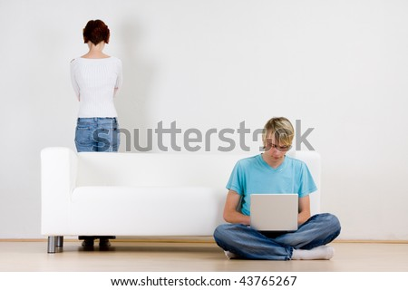 Young couple in room with man on laptop and woman standing behind couch. - stock photo