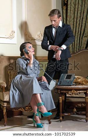Young couple in royal interior. Woman talking on the phone. Men check his watch. - stock photo