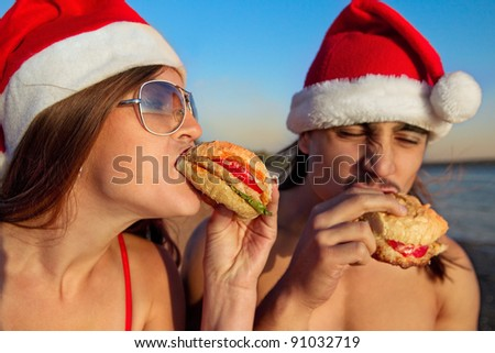 Young couple in Santa hats eating a fast food hamburger at the tropical beach, focus on the burger - stock photo