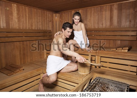 Young couple in sauna. Handsome man pouring water on hot rocks in sauna  - stock photo
