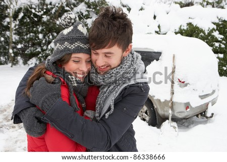 Young couple in snow with car - stock photo
