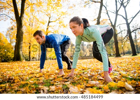 Young couple in starting position prepared for running in autumn nature