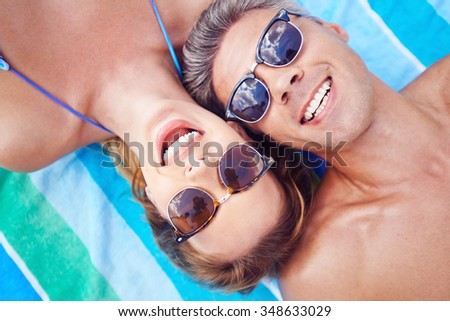 Young couple in sunglasses looking at camera while relaxing at summer resort - stock photo