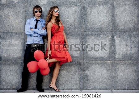 Young couple in sunglasses posing near wall - stock photo