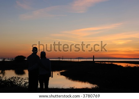 young couple in sunset - stock photo
