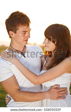 Young couple in sunset embraced together - stock photo