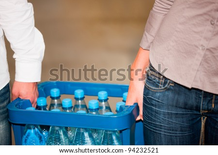 Young couple in supermarket buying beverages together, close-up on box - stock photo