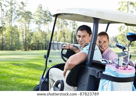 Young couple in the car for golf - stock photo