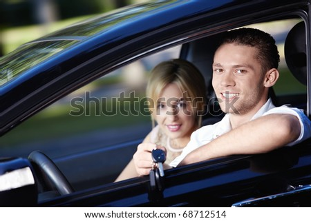 Young couple in the car with the keys of the car - stock photo