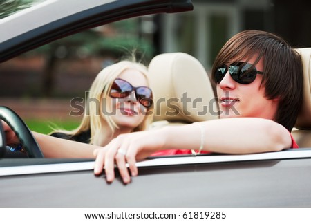 Young couple in the convertible car. - stock photo