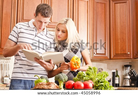 Young couple in the kitchen read an open recipe book. The counter is full of fresh vegetables. Horizontal shot. - stock photo
