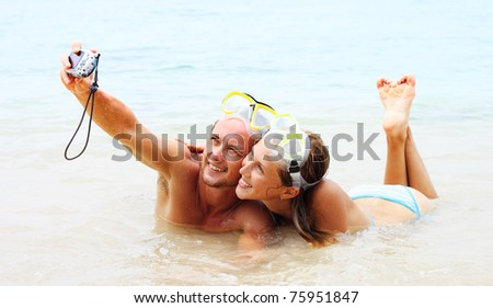 Young couple in the masks making photo of themselves in the sea - stock photo