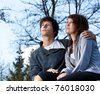Young couple in the park, blue sky in background - stock photo