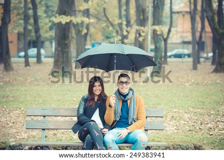 young couple in the park during autumn season outdoor - lovers valentine under umbrella sitting in a bench - stock photo