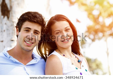 Young couple in the park looking at camera