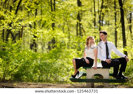 Young couple in the park sitting on the bench - stock photo