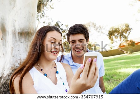 Young couple in the park with mobile phone