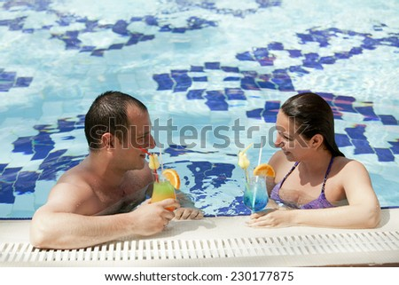 Young couple in the pool. - stock photo
