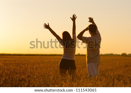 Young couple in the wheat field on sunny summer day. - stock photo