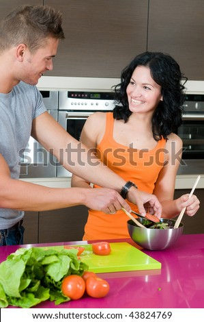 young couple in their kitchen with salad