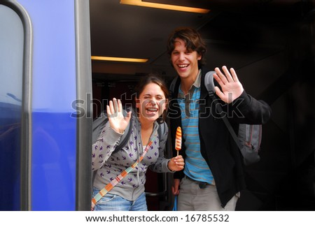 Young couple in their twenties laughing and waving goodbye from departing train in holland - stock photo